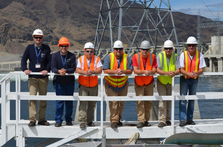Group of Grant PUD employees standing near dam railing