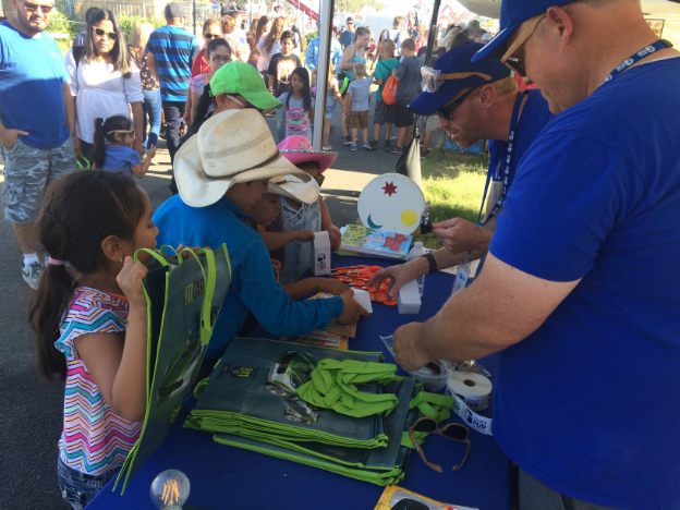 Grant PUD employee giving out freebies at the fair booth